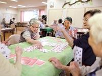 קשישים משחקים קלפים במעון / צילום: בלומברג
