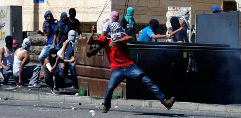 פלסטינים מיידים אבנים בשכונת שועפט בירושלים / צילום: רויטרס