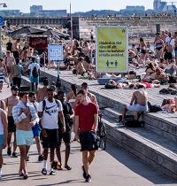 שלט שמזכיר לשמור על ריחוק חברתי בגלל הקורונה בעיר מאלמו בשבדיה, יולי. גל החום בקיץ הביא להתגודדות בחופים ובאתרי הנופש / צילום: רויטרס
