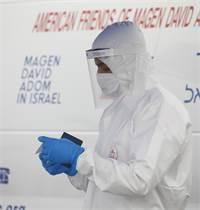 """חובש של מד""""א לפני ביצוע בדיקת קורונה / צילום: Ariel Schalit, AP"""