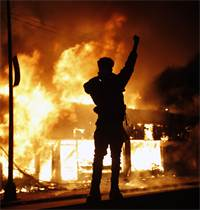 מפגין מול בית עסק להחלפת צ'קים שעולה באש ביום שישי במיניאפוליס, העיר שבה נרצח ג'ורג' פלויד בן ה-46  / צילום: John Minchillo, AP
