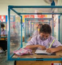 תלמידה בתאילנד יושבת מאחורי מסך מגן מפלסטיק / צילום: Gettyimages ישראל - Lauren DeCicca