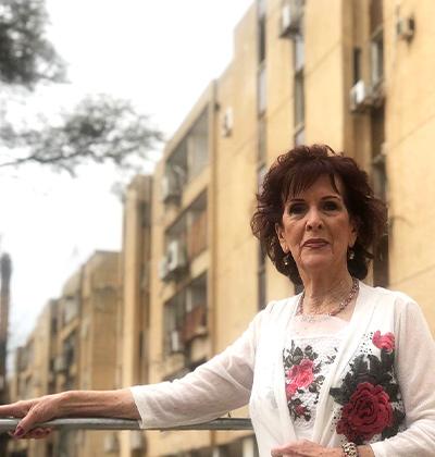 הדיירת רחל גרינברג על רקע הבניינים, לפני ההריסה / צילום: מיכל ארבל