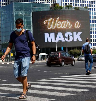 אדם עם מסכה הולך ליד קניוני עזריאלי בתל אביב / צילום: Corinna Kern, רויטרס