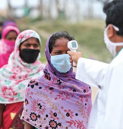 מהגרת עבודה בהודו עובדת מדידת חום כדי לקבל אישור לעלות על רכבת בחזרה לביתה / צילום: Channi Anand, Associated Press