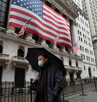 אדם עם מסכה עובר ליד בניין בורסת ניו יורק / צילום: Mark Lennihan, AP