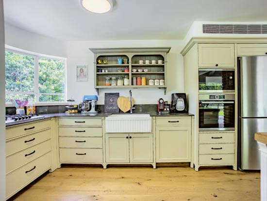 יחידת המדפים הפתוחים היא החלק האישי במטבח. הכיור במרא הכפרי משתלב בין הגוונים הקלילים  / צילום: לירן שמש
