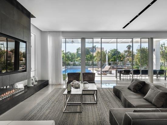 הסלון פונה מצד אחד לקיר שעליו ממוקמים הטלוויזיה והקמין, ומצד שני פתוח בוויטרינה לחצר / צילום: עודד סמדר