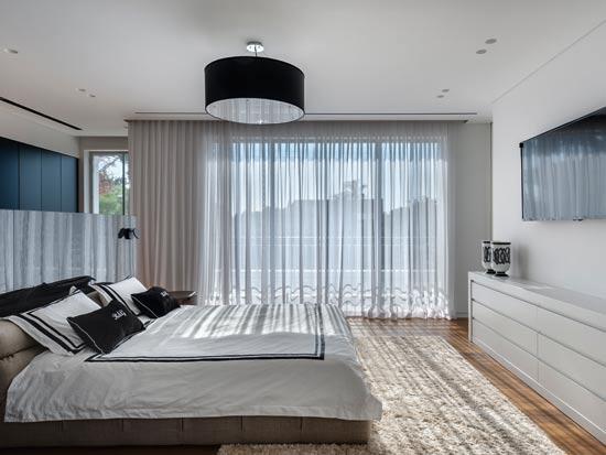 חדר שינה הורים. גווניו ממשיכים את עיצוב הבית, ושולבו בו וילונות ושטיח המעניקים מראה חמים / צילום: עודד סמדר