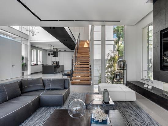 החלל הכפול מחלק את הבית לשניים - מצד אחד המטבח, ומצד שני הגינה, הסלון ופינת האוכל. מדרגות הבית נשענות על חזית זכוכית שהיא הפטיו המתחיל מקומת המרתף, ומלווה את כל הקומות / צילום: עודד סמדר