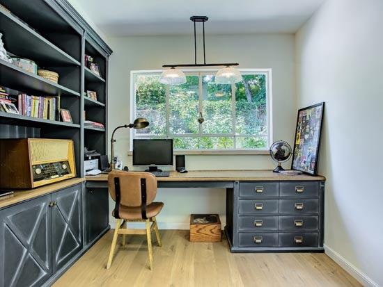 חדר העבודה במפלס הכניסה נע בין הקליל לכבד - רהיט במבנה קלאסי מסוגנן, וצביעה מיוחדת שיוצרת מראה אמנותי/ צילום: לירן שמש