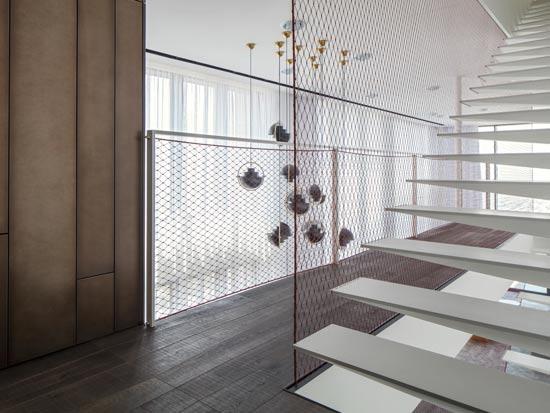 מדרגות הפלדה צבועות בגון הקיר, ומבליטות את מעקה הרשת האדומה / צילום: עמית גרון