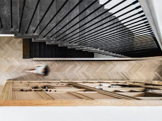 גרם המדרגות שמוביל לקומת המגורים תוכנן כציר ארכיטקטוני, בקרבת ספריית האלון ושירותי האורחים. שלחי המדרגות עטופים אבן בלוסטון כהה ודרמטית - צילום: איתי בנית