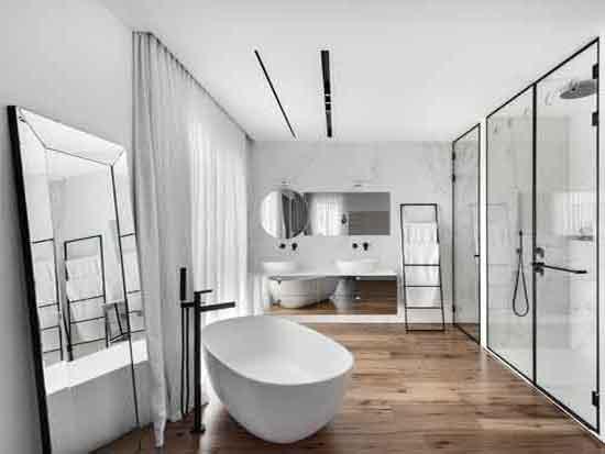 """חדר הרחצה פתוח לחדר השינה, עם אמבטיה  פרי סטנדינג במרכזו / צילום: עודד סמדר, יח""""צ"""