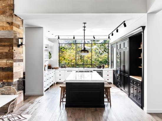 המטבח רחב הידיים כולל מזווה וכן פתרונות אחסון רבים. הוא תוכנן בקווים קלאסיים ובצבעוניות מונוכרומטית, ואת החום מכניסים כיסאות העץ, משטחי הבוצ'ר, ידיות ומנורות הפליז / צילום: איתי בנית
