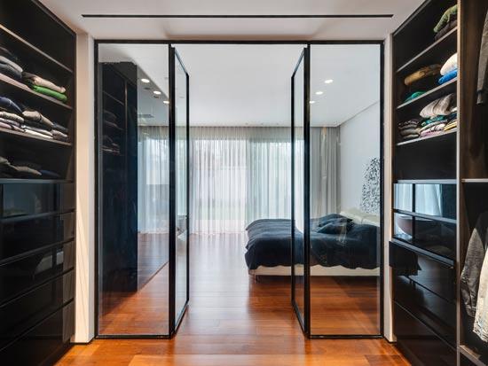 מבט מחדר הארונות אל חדר השינה. בין שני החללים מפרידות דלתות זכוכית שקופה וברזל שחור. למרות שסוויטת השינה ממוקמת בקומת הכניסה ובסמוך למטבח, נוצרה הפרדה אפקטיבית בין האגפים / צילום: עודד סמדר