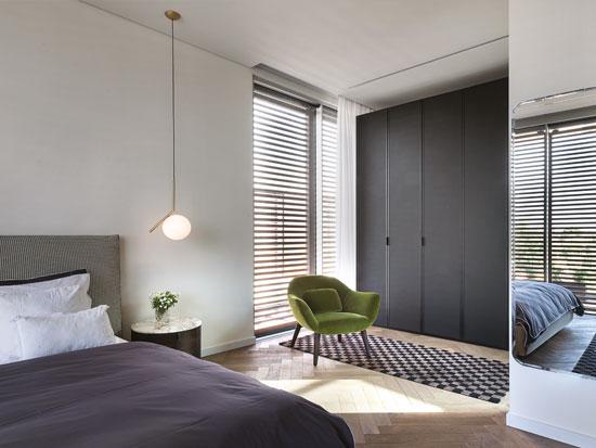 פינת ישיבה בחדר השינה של ההורים, על רקע ארון עם דלתות מזכוכית שחורה בגוון מט / צילום: עמית גושר
