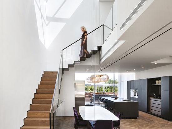 המדרגות עשויות ברזל בשילוב עץ, מעוגנות לקיר מצד אחד וקונזוליות מצדן השני. מעקה זכוכית וברזל מוסיף למראה המינימליסטי / צילום: עמית גושר
