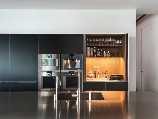 קיר הארונות הגבוהים מאפשר אחסון רב. במרכזו דלת עם תאורה פנימית, מכונת קפה ומכשירי חשמל מנירוסטה, ש'שוברים' את החזית האפורה /  צילום: עודד סמדר