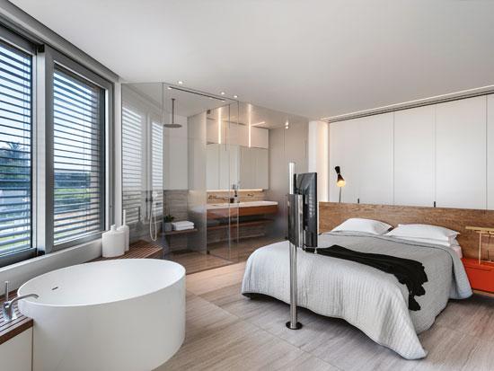 חדר השינה. הגב הרחב של המיטה המרכזית חוצץ בינה לבין אזור הארונות. בפינת החדר שולב אמבט עגול לצד ספסל עץ טיק, שממנו ניתן להשקיף לכיוון צפון והים / צילום: עודד סמדר