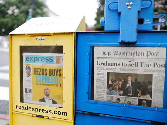 עיתונים שמבשרים על העסקה בה רכש בזוס את הוושינגטון פוסט / צילום: רויטרס - Jonathan Ernst