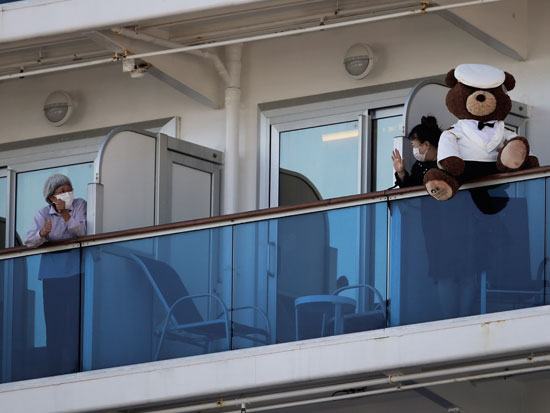 נוסעים מציצים ממרפסות התאים. שהו שבועיים בתא קלסטרופובי והורשו לצאת לשעה ביום לסיפון / צילום: AP - Jae C. Hong