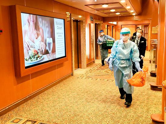 נציגי שירותי הבריאות היפניים על הספינה. נוסעים טענו שלא היו ממוגנים באופן מספק והתהלכו בחופשיות ביניהם / צילום: AP - Daxa_Tw