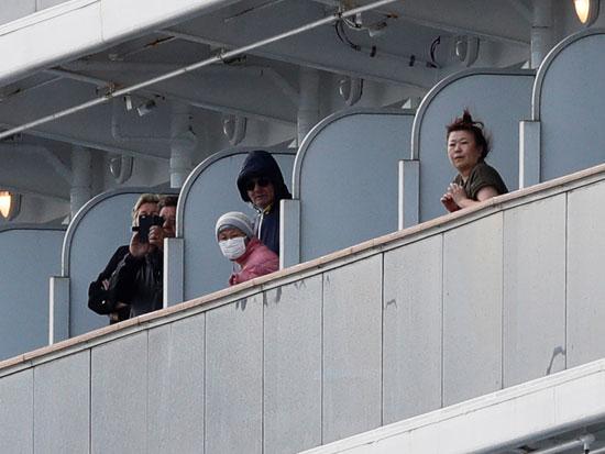 נוסעים מציצים ממרפסות התאים. שהו שבועיים בתא קלסטרופובי והורשו לצאת לשעה ביום לסיפון / צילום: רויטרס - Kim Kyung Hoon