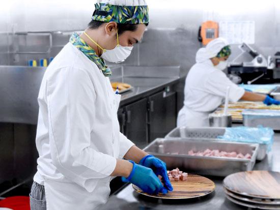עובד במטבח האונייה. עברו משירותי מסעדה לחלוקת אוכל ל־1,337 תאים / צילום: מתוך אתר חברת princess