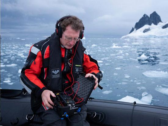 """המדען טים לואיס מאזין לקרחונים מתנפצים. """"הפצפוץ שאנחנו שומעים הוא כיסי האוויר שנדחסו לתוך הקרח ועכשיו משתחררים"""" / צילום: Abbie Trayler-Smith - Greenpeace"""