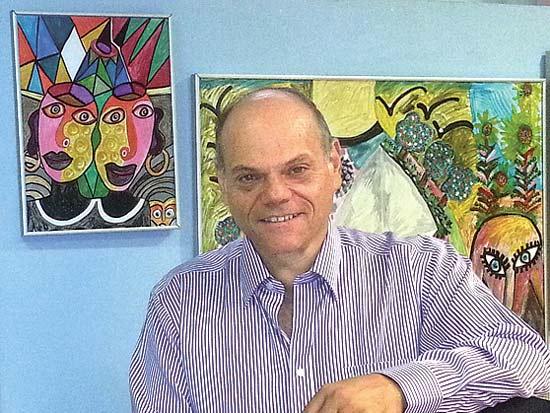 פיני גולדשטיין על רקע יצירותיו, תערוכת יחיד / צילום: יחצ