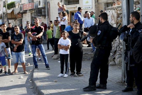 פלשתינאים מול עמדת שמירה של שוטרים ישראליים/צילום: רויטרס