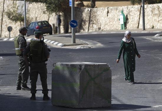 פלשתינאית מול עמדת שמירה של שוטרים ישראליים/צילום: רויטרס