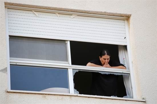 אישה מביטה מחלון שבור לאחר מטח רקטות לשדרות / רויטרס
