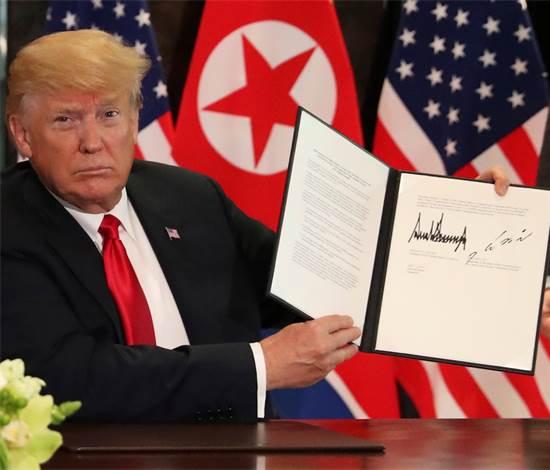 טראמפ עם המסמך החתום / צילום: ג'ונתן ארנסט, רויטרס