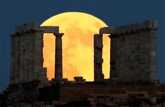 ירח מלא מאחורי המזבח של פוסידון ליד אתונה, יוון הערב / צילום: רויטרס