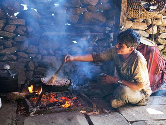 בעל הגסטהאוס מכין דאל־באט, המאכל הלאומי, בשיטה המסורתית / צילום: שאטרסטוק