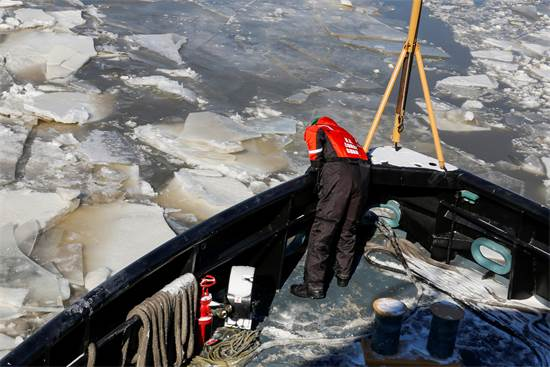 איש משמר החופים עובד על סירה בנהר ההדסון הקפוא בניו יורק / צילום: REUTERS/Eduardo Munoz