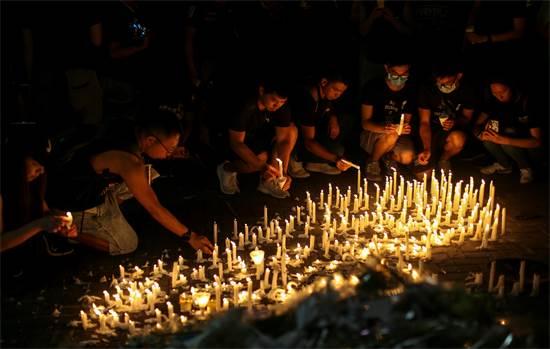 מפגינים מדליקים נרות לזכר מפגין שנהרג לאחר שנפל מפיגומים / צילום: Athit Perawongmetha, רויטרס