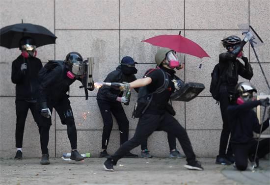 מפגין זורק בקבוק תבערה במחאה בהונג קונג בסוף השבוע האחרון / צילום: Adnan Abidi, רויטרס