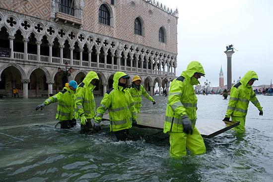 עובדים בכיכר סיינט מארק בונציה המוצפת / צילום: Manuel Silvestri, רויטרס