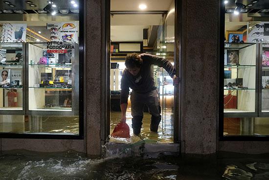 אדם מנסה להציל את החנות המוצפת שלו, ונציה, היום / צילום: Manuel Silvestri, רויטרס