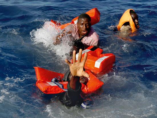 פליטים לובים מנסים להחזיק עצמם מעל המים / צילום: רויטרס - Darrin Zammit Lupi
