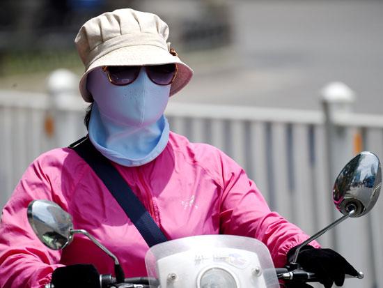 אישה עם מסיכת הגנה מהשמש בהנאן, סין / GettyImages ישראל