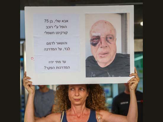 טלי רובינשטיין  מניפה שלט שמתאר את מה שקרה לאביה / צילום: שלומי יסף