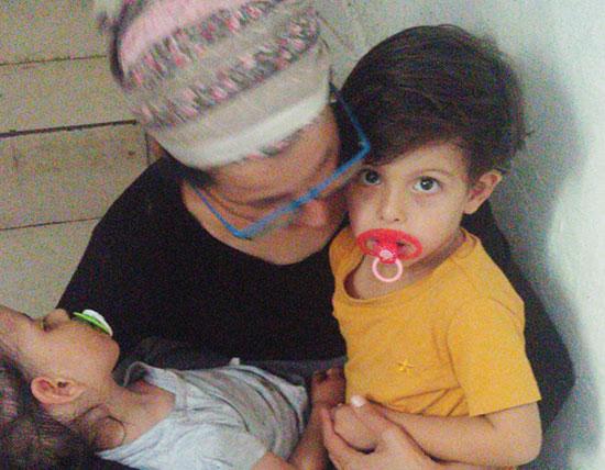 נחמה נאוגווקר בזמן אזעקה, אתמול. עם הילדים איתן (מימין) ודביר  / צילום: תמונה פרטית