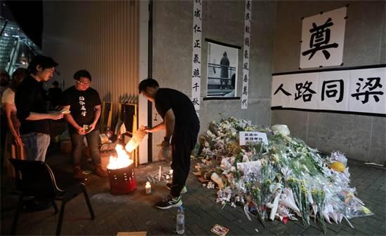 מפגינים מדליקים נרות ושמים פרחים לזכר מפגין שנהרג לאחר שנפל מפיגומים / צילום: Athit Perawongmetha, ר