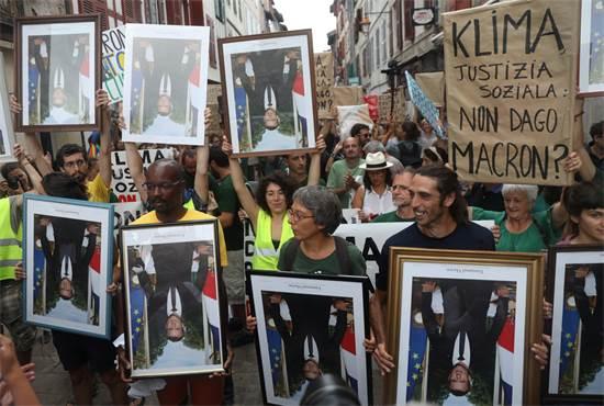 מפגינים עם תמונות הפוכות של הנשיא מקרון / צילום: סרג'יו פרז, רויטרס