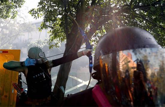 מפגין יורה בחץ וקשת במחאות בהונג קונג בסוף השבוע האחרון / צילום: Athit Perawongmetha, רויטרס