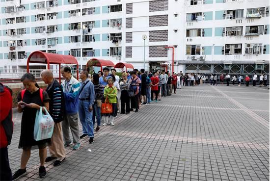 תושבים בהונג קונג עומדים בתור כדי להצביע בבחירות / צילום: Adnan Abidi, רויטרס